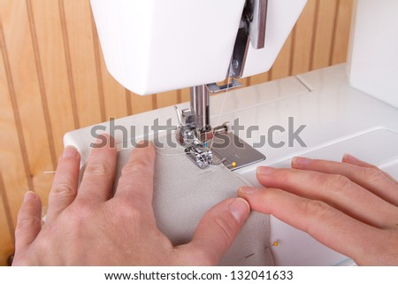 Sewing tan fabric on sewing machine - stock photo