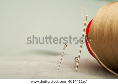 Sewing textile or cloth. Work table of a tailor. Detail of a needle with thread in the workroom reel of thread, and natural fabric. . Shallow depth of field. Focus on needle. - stock photo