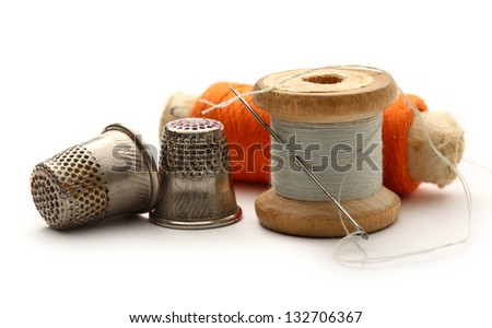 Sewing thimbles, bobbins and needle - stock photo