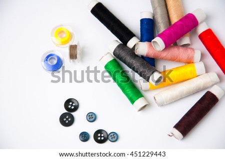 Sewing thread and buttons isolated on white background - stock photo