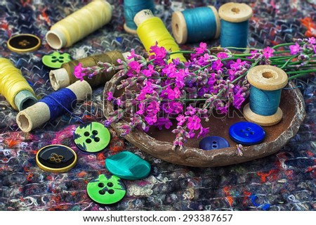 sewing thread and buttons on the background batting is decorated with blooming lavender.Photo tinted. - stock photo