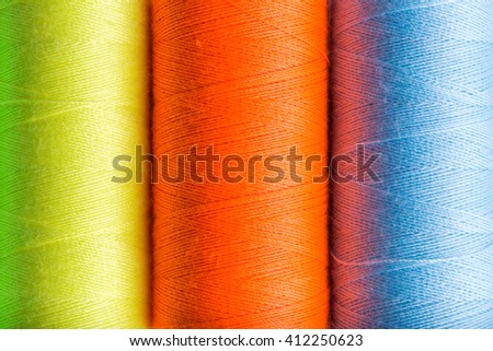 Sewing threads of different colors stacked side by side on a white background - stock photo