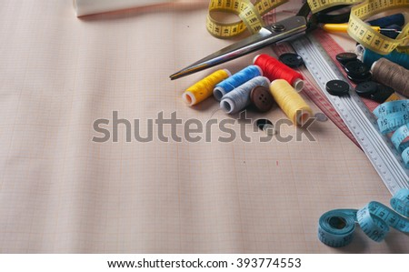 Sewing tools and accessories closeup on graph paper with copy space. Sewing background - stock photo