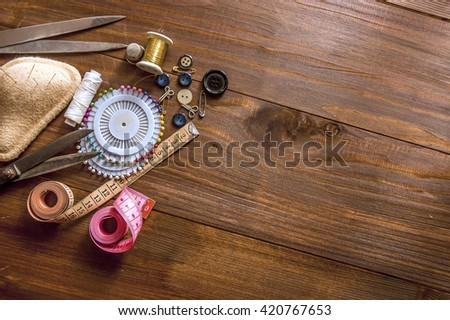 sewing tools and sewing kit on the wooden background - stock photo