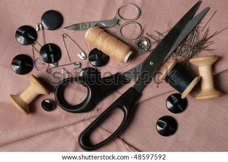 Sewing tools. Thread on spool, scissors, buttons and needles on threaded texture. - stock photo