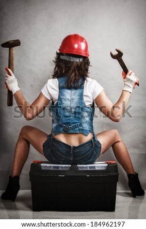 Sex equality and feminism. Back of sexy girl sitting on toolbox and holding wrench spanner and hammer tools on gray. Young attractive woman working as construction worker. Studio shot. - stock photo