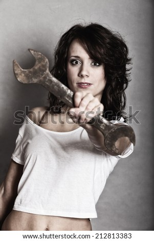 Sex equality and feminism. Sexy girl holding wrench spanner tool. Attractive woman working as repairman or mechanic. - stock photo