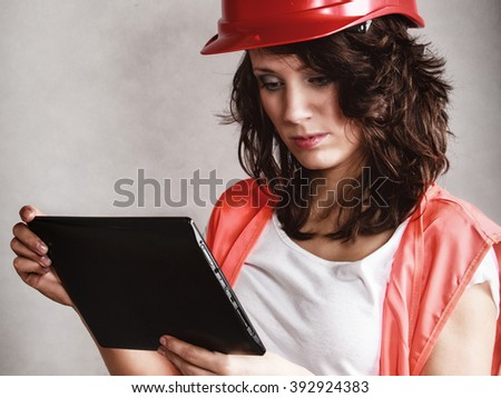 Sex equality and feminism. Sexy girl in workwear safety helmet and orange vest using tablet touchpad ipad on gray. Young attractive woman as construction worker. Technology. - stock photo