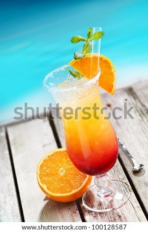 Sex on the beach Cocktail on wooden planks in front of a blue swimming pool or the ocean. For Drinkable Concepts visit my Portfolio. - stock photo
