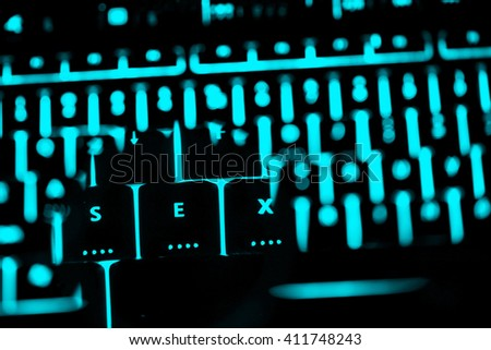 Sex text on the illuminated buttons of the keyboard by night. Internet pornography concept.  - stock photo