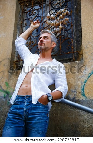 Sexi Man in a white shirt and ornamental window on background. And Dream Catcher  - stock photo