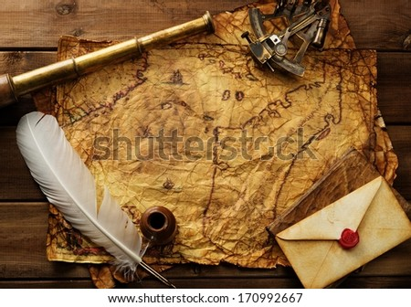 Sextant, spyglass and envelope on vintage map over wooden background  - stock photo