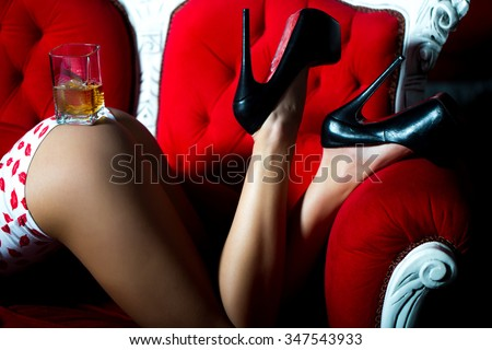 Sexual beautiful female buttocks and legs of young woman with straight slim flexible body in underwear with kiss print and high heeled shoes with glass of alcoholic beverage of brandy or whisky - stock photo