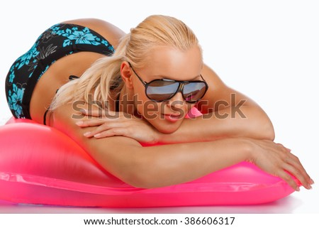Sexual blond woman in sunglasses lying in a pink water matress. - stock photo
