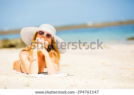 Sexual brunette girl take sunbath on the beach, happy female in  swimwear in sunglasses and white hat enjoying summer holidays leying on white sand. Holidays, vacation, lifestyle concept. Copyspace - stock photo
