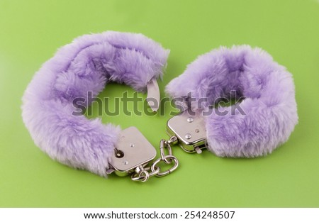 Sexual cuffs with purple fur on a green background - stock photo