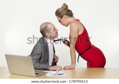 Sexual games and flirting in the workplace with a sexy blonde secretary or female colleague pulling her boss towards her by his tie with a leery smile - stock photo