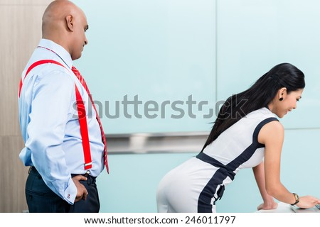 Sexual harassment at workplace, boss looking at butt of secretary - stock photo