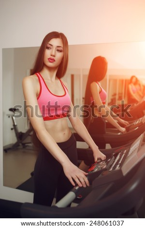 Sexual long-haired brunette, athletic appearance, is engaged on the treadmill at the gym. Instagram toning effect. - stock photo