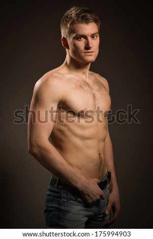 Sexual muscular man posing over dark background - stock photo