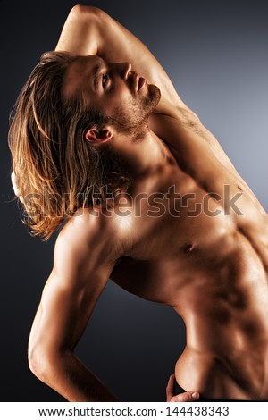 Sexual muscular nude man posing over dark background. - stock photo