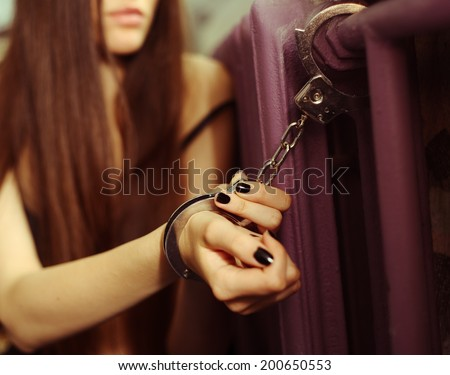 Sexual slavery. Young woman locked with handcuffs - stock photo