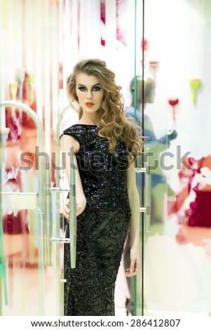 Sexual young blonde woman in back dress in sequins standing on store background, vertical picture - stock photo