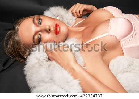 Sexual young woman in a beautiful pink lingerie lying on a white fur over black background.  - stock photo