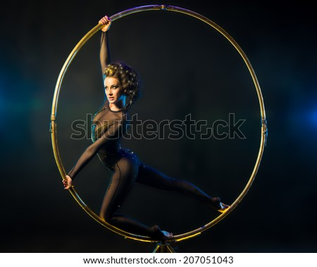 Sexy acrobat performs gymnastic stunt on a gold ring - stock photo
