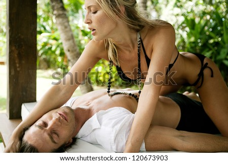 Sexy and attractive couple being passionate while lounging on a tropical garden bed while on vacations in an exotic lush destination, outdoors. - stock photo