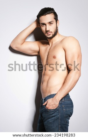 Sexy and confident. Handsome young muscular man with perfect body posing against grey background - stock photo
