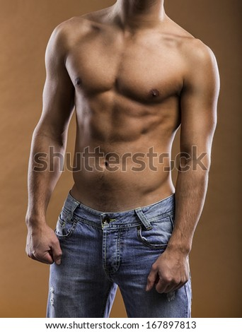 Sexy and handsome young man posing and showing his muscles - stock photo