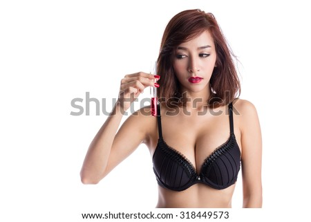 Sexy asian woman in black lingerie holding a tube, with red liquid inside, fashion, science and experiment concepts. - stock photo