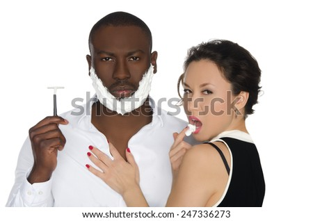Sexy asian woman licking the foam from his cheeks dark-skinned men with razor isolated on white - stock photo