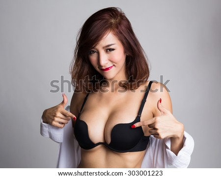 Sexy asian woman showing her sexy breast in black bra or  lingerie with shirt opened, and pointing at her breast - stock photo