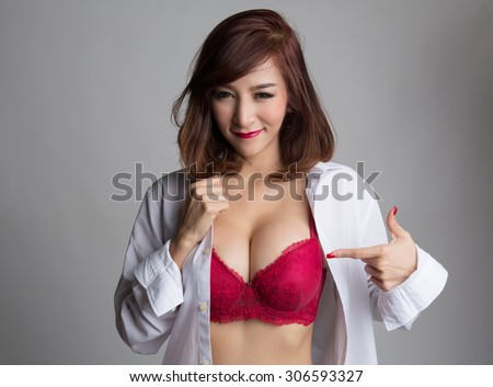Sexy asian woman showing her sexy breast in red bra or  lingerie with hand pointing at her breast, shirt opened by her hand - stock photo