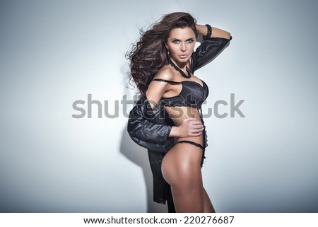 Sexy attractive brunette woman posing in elegant black lingerie and jewelry, looking at camera. - stock photo