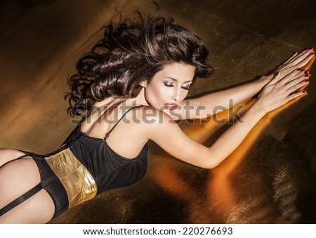 Sexy attractive brunette woman posing in elegant black lingerie with closed eyes - stock photo