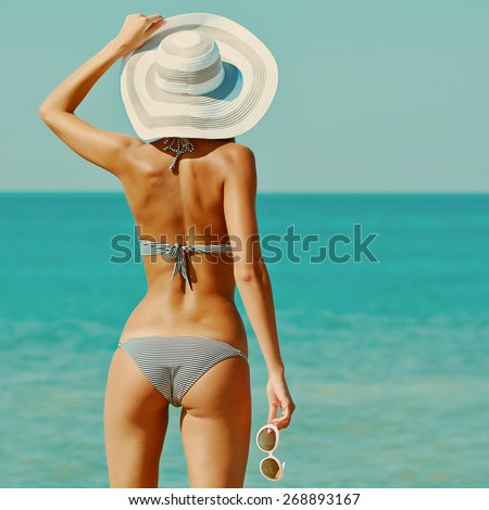 Sexy back of a beautiful woman in bikini on sea background. Sexy buttocks. Retro vintage toned image, film simulation. - stock photo