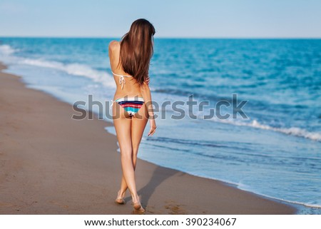 Sexy back of a beautiful woman in bikini on sea background. Sexy buttocks. Soft sunset bright. - stock photo