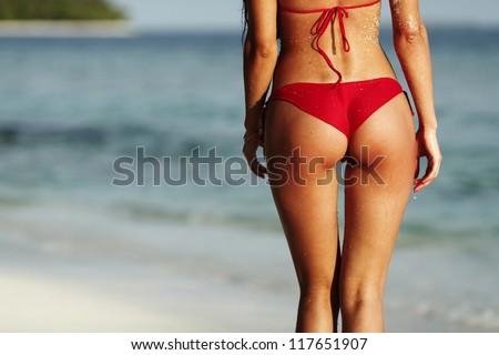 Sexy back of a beautiful woman in red bikini on sea background - stock photo