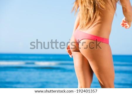 Sexy back of a beautiful woman on tropical beach in small sexy bikini  - stock photo