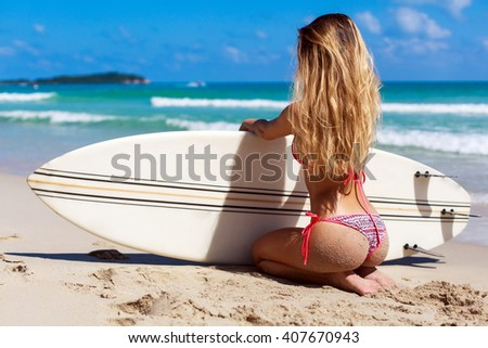 Sexy back of tanned sporty longhaired woman having fun in summer on vacation on ocean seashore on the beach. Pretty girl in bikini sitting on sand with surf board  - stock photo