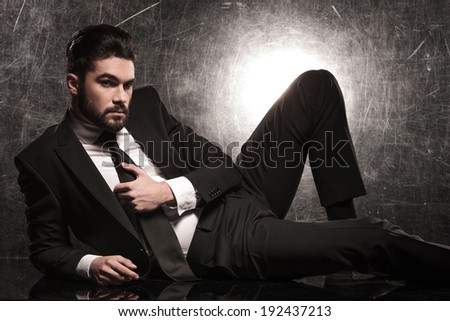 sexy bearded business man holding his tie while lying on the floor - stock photo