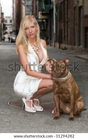 Sexy, beautiful blond woman with brown pit bull terrier dog on a leash in grungy urban alley - stock photo