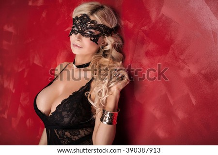 Sexy beautiful blonde woman posing in elegant black lingerie and mask, looking at camera. Perfect body. Red background. - stock photo