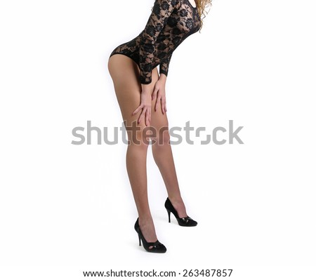 Sexy beautiful body shot of young woman wearing black lace lingerie. Perfect long legs on high heels shoes, studio shot. Gorgeous woman body wearing black corset on white background - stock photo