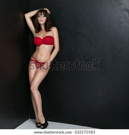 Sexy beautiful brunette lady posing in fashionable red lingerie. Sensual woman with long slim legs and glamour makeup. Studio shot. - stock photo