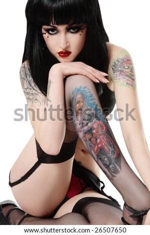 Sexy beautiful brunette with tattoos sitting in white background - stock photo