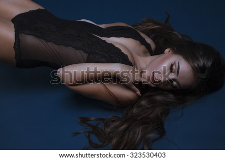 Sexy beautiful brunette woman lying on blue background in sensual black lingerie. Attractive fashion model. Studio shot, horizontal - stock photo